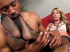 Tough black guy is fondling white lady`s nice feet in black pantyhose.